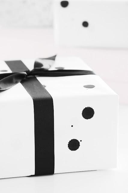 Weißes Geschenkpapier mit schwarzen Klecksen