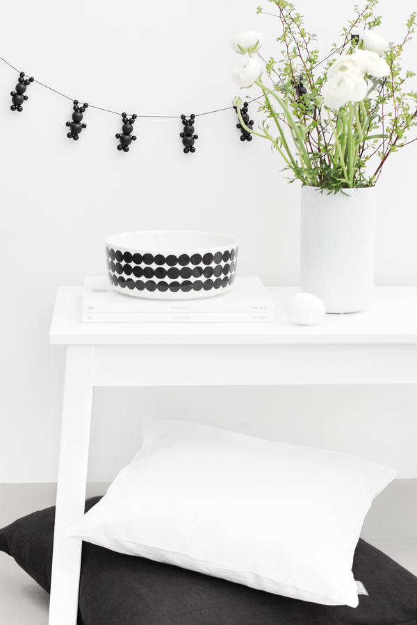 Girlande aus schwarzen Osterhasen an weißer Wand
