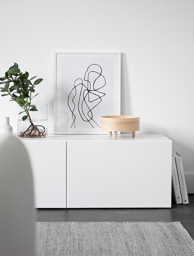 Holzschale mit Standfüßen auf weißem Sideboard